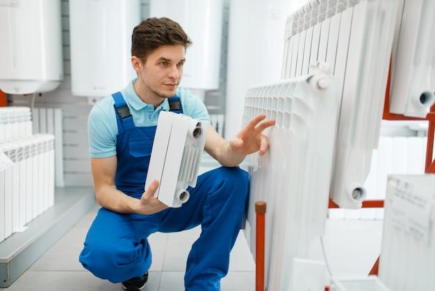 Plombier montre la section du radiateur de chauffage, la plomberie