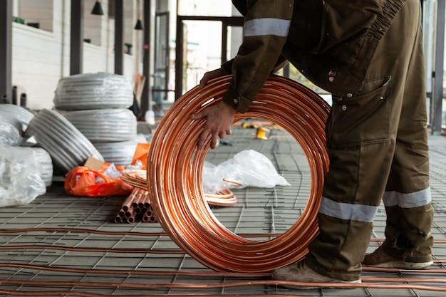 Plombier pose de tuyaux en cuivre sur le sol avec chauffage chaud