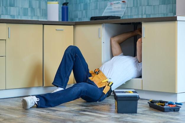 Plombier professionnel de travail efficace portant la ceinture à outils fixant le tuyau d'évier à l'intérieur