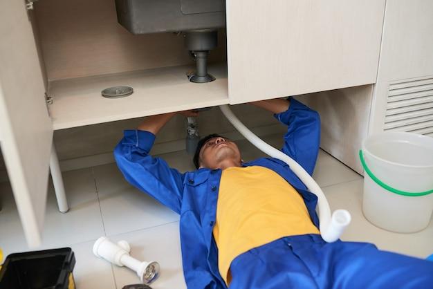 Plombier réparant une fuite de tuyau
