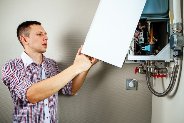 Plombier s'attache à essayer de résoudre le problème de l'équipement de chauffage résidentiel. réparation d'une chaudière à gaz