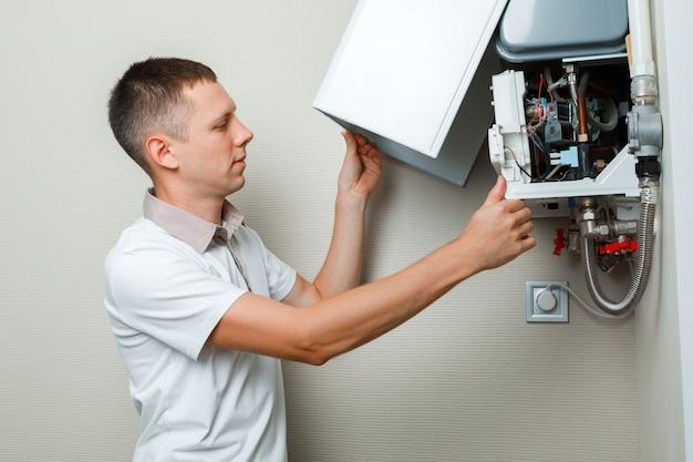Le plombier s'attache à essayer de résoudre le problème avec l'équipement de chauffage résidentiel. réparation d'une chaudière à gaz
