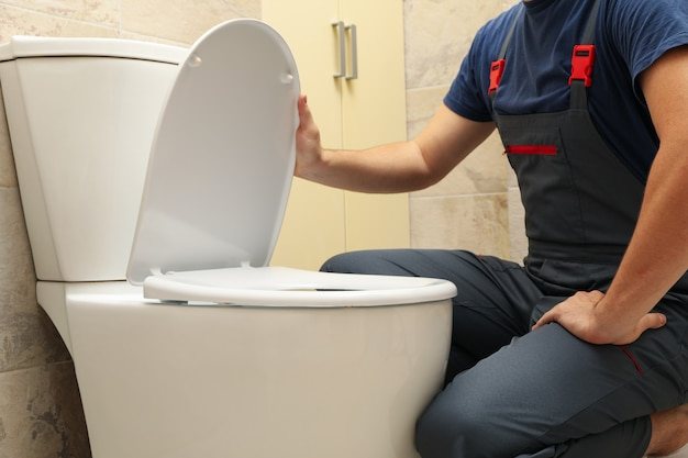 Le plombier en salopette répare les toilettes