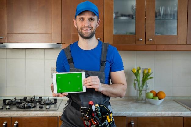 Plombier tient une tablette numérique avec un écran vert dans la cuisine