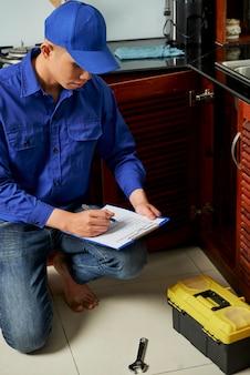Plombier travaillant dans la cuisine