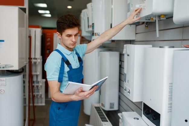 Plombier en uniforme choisissant la chaudière à la vitrine en magasin de plomberie.