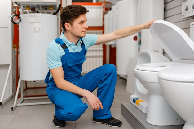 Plombier en uniforme choisissant les toilettes à la vitrine en magasin de plomberie.