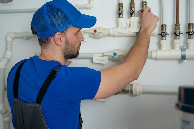 Un plombier en uniforme est en train de fermer et d'ouvrir les robinets