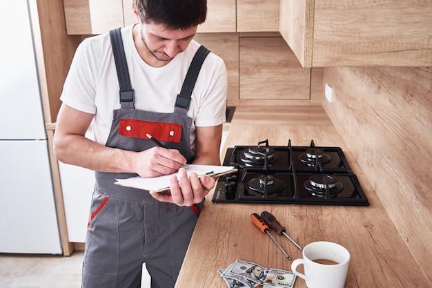 Un plombier en uniforme signe un contrat de services dans la cuisine