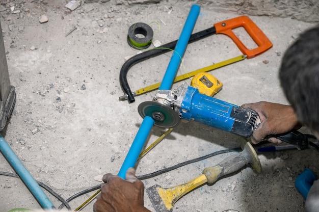 Plombier utilisant une scie électrique coupant un tuyau en pvc lors de la rénovation de la salle de bain