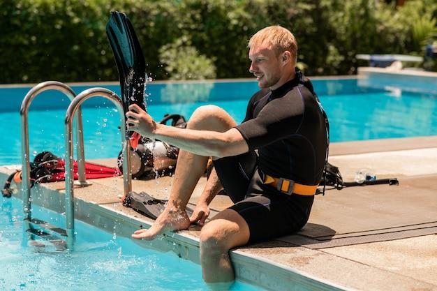 Plongeur mâle mettant des palmes avant de sauter en mer pour plonger