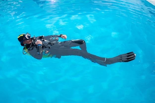 Le plongeur nage sur le dos dans la piscine