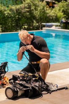 Un plongeur teste un détendeur après une plongée sous-marine