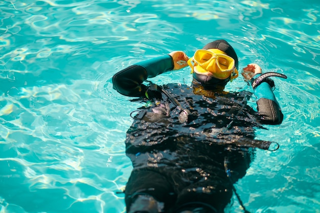 Plongeuse en équipement de plongée pose dans la piscine, vue de dessus, cours à l'école de plongée. apprendre aux gens à nager sous l'eau, à la natation en salle. femme avec aqualang