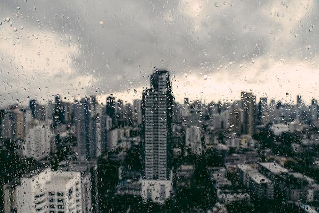 Pluie au-dessus de bangkok: paysage urbain hors de la vue derrière la vitre avec des gouttes de pluie.