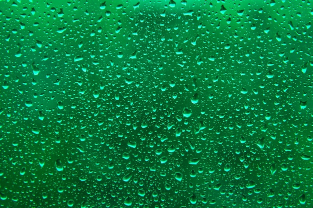 La pluie d'eau tombe sur une surface verte acide en arrière-plan. toile de fond abstraite.