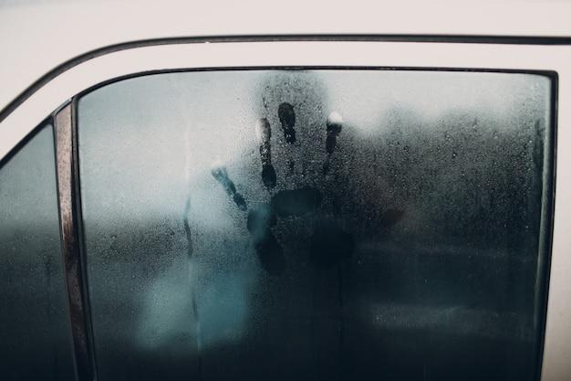 Pluie et empreinte de main sur la fenêtre de la voiture