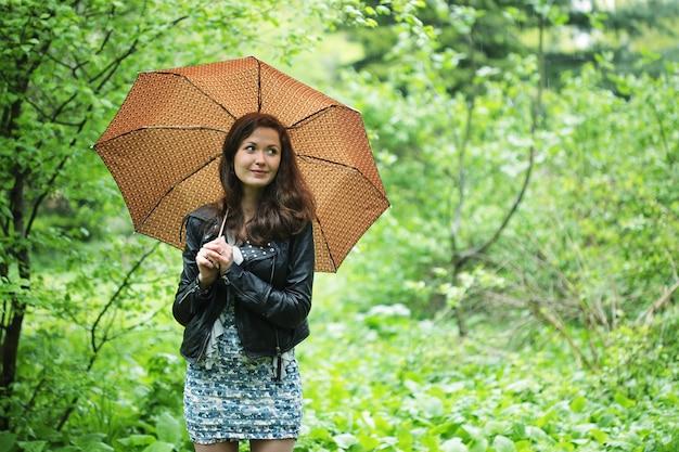 Pluie d'été. femme dans le jardin.