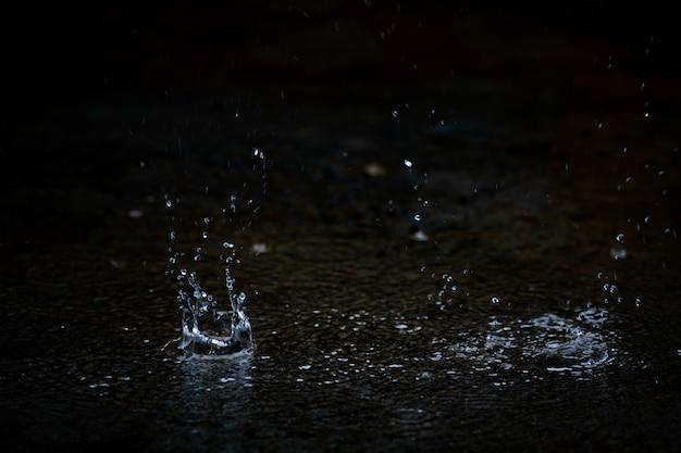 Pluie de gouttelettes et éclaboussures sur un sol sombre pendant la saison estivale