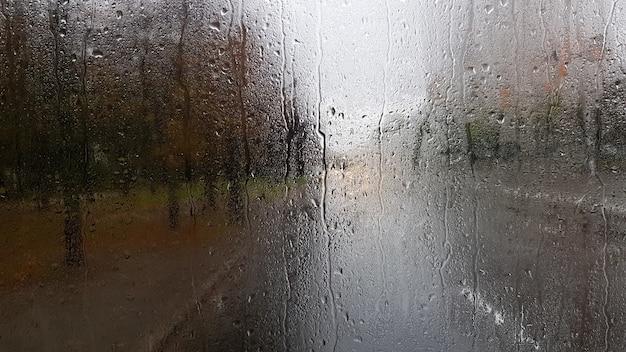 Pluie sur la lunette arrière d'une voiture en automne. vue intérieure de la route avec des voitures en mouvement dans la ville à travers la fenêtre de la voiture avec des gouttes de pluie. conduire une voiture dans le champ de vision de la lunette arrière.