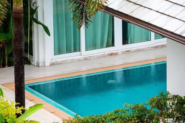 La pluie tombe sur le jardin de la piscine dans la villa