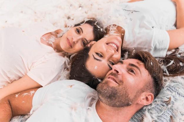 Plume blanche sur les amis souriants allongé sur le lit