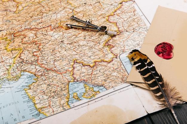 Plume, compas, épices, enveloppe se trouvent sur la vieille carte jaune