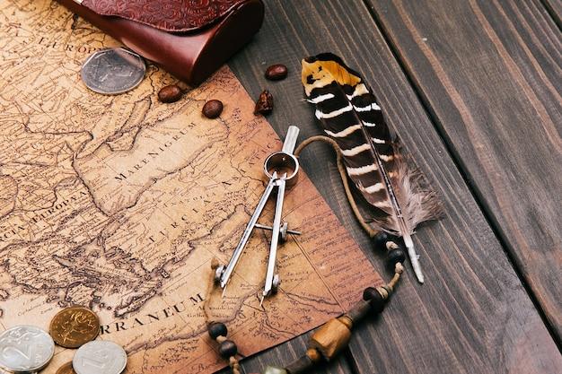 Plume, compas, grains de café, pièces de monnaie se trouvent sur la vieille carte jaune