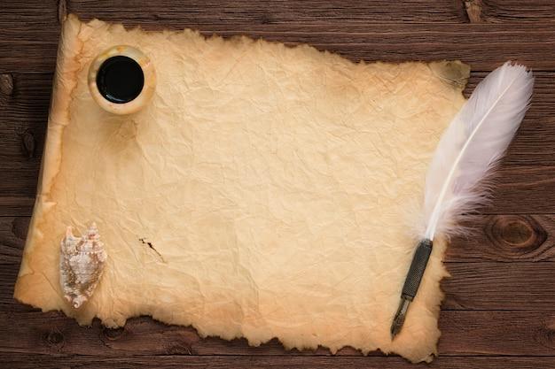 Plume avec encrier sur fond de papier vintage et table en bois
