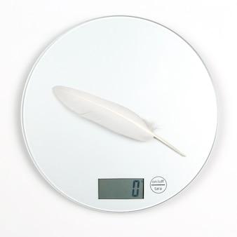 La plume d'oiseau blanc est pesée sur une balance numérique