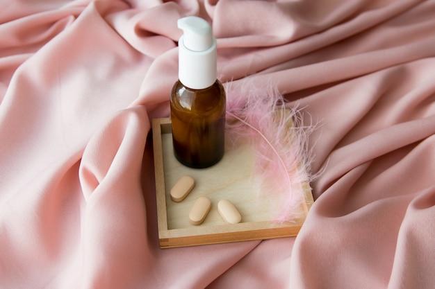 Plume rose avec une bouteille de crème brune, des comprimés sur la table de la texture.