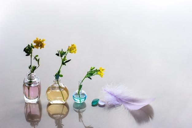 Une plume avec une teinte rose se trouve à côté des bouteilles d'huiles aromatiques copy space