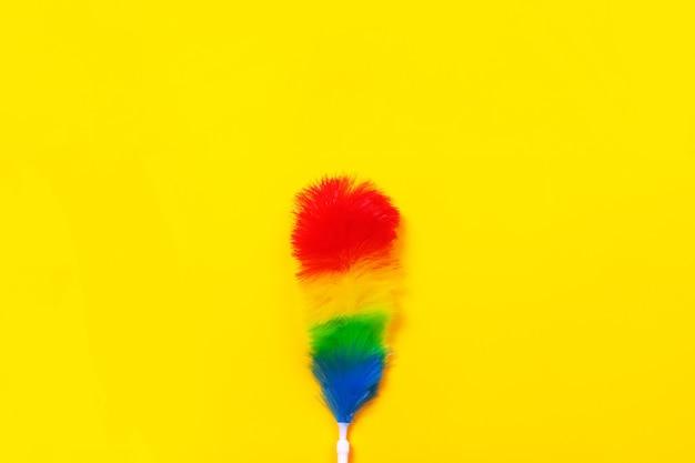 Plumeau coloré sur fond jaune. concept de nettoyage.