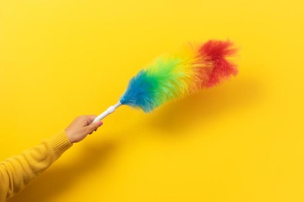 Plumeau coloré à la main sur fond jaune. concept de nettoyage.