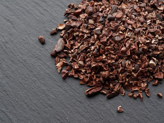 Plumes de cacao crues. fond sombre avec espace de copie. vue de dessus.