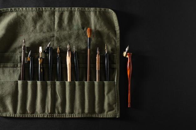 Plumes de calligraphie dans un étui à crayons
