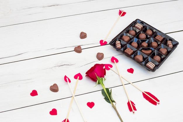 Plumes d'ornement sur les baguettes avec petits coeurs près de fleurs et bonbons