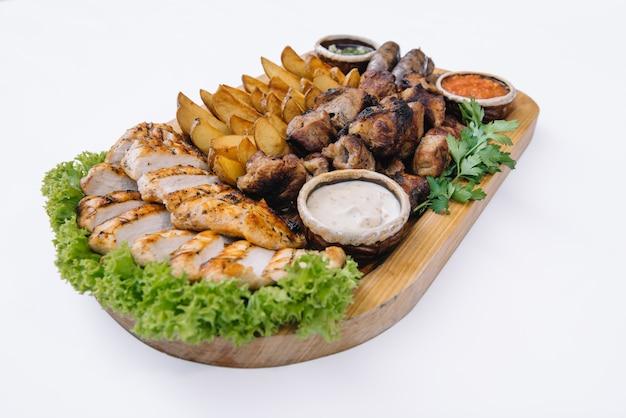 La plupart des plats de viande - brochettes de bœuf, saucisses, champignons grillés, pommes de terre, tomates et sauce. le meilleur choix pour une bière. fermer.