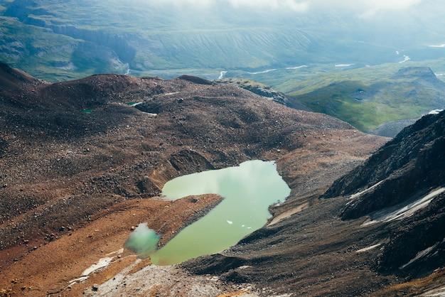 Le plus beau lac glaciaire de couleur vert acide. lac de montagne émeraude et petite rivière dans la vallée des montagnes. morceaux de glace sur l'eau parmi les rochers et les pierres. superbe lac alpin aux tons verts inhabituels.