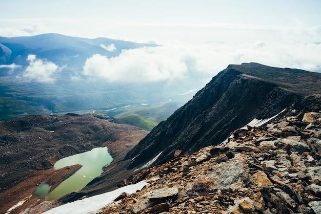 Le plus beau lac glaciaire de couleur vert acide. lac de montagne d'émeraude près de la grande montagne rocheuse noire. superbe lac alpin aux tons verts inhabituels parmi les rochers et les nuages bas au-dessus de la vallée verte des hautes terres.