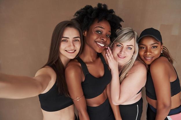 Plus besoin de photographe. groupe de femmes multiethniques debout contre l'espace brun