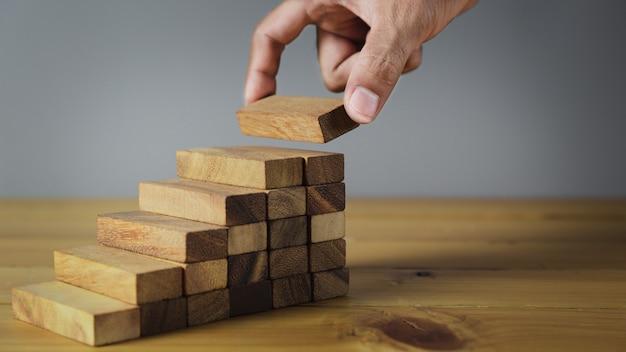 Plus près des mains des hommes d'affaires, empiler des blocs de bois en marches, concept de réussite de la croissance de l'entreprise - image