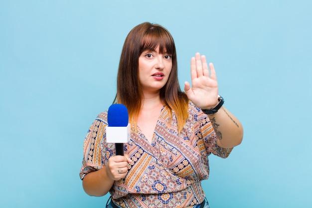 Plus la taille femme à la recherche sérieuse, sévère, mécontente et en colère montrant la paume ouverte faisant le geste d'arrêt