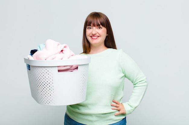Plus la taille femme souriant joyeusement avec une main sur la hanche et une attitude confiante, positive, fière et amicale