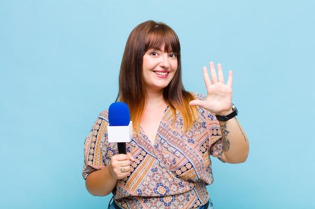 Plus la taille femme souriante et à la recherche amicale, montrant le numéro cinq ou cinquième avec la main en avant, compte à rebours