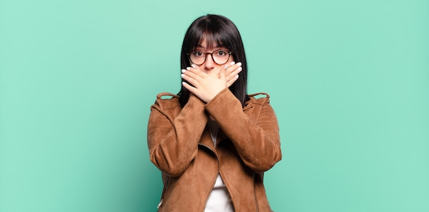 Plus la taille jolie femme couvrant la bouche avec les mains avec une expression choquée et surprise, en gardant un secret ou en disant oups