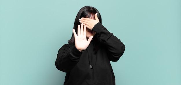 Plus la taille jolie femme couvrant le visage avec la main et mettant l'autre main à l'avant pour arrêter la caméra, refusant les photos ou les images
