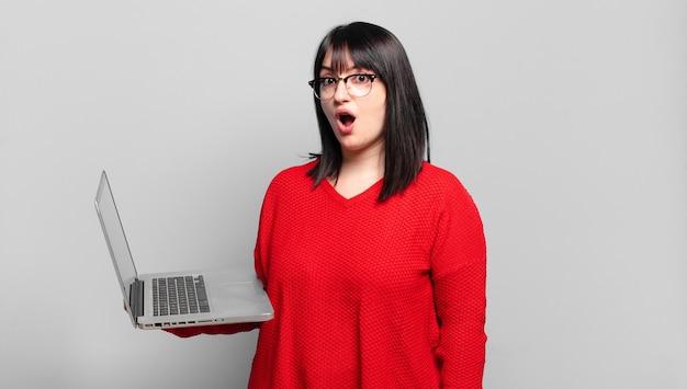 Plus la taille jolie femme à la recherche très choquée ou surprise, regardant avec la bouche ouverte disant wow