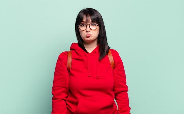 Plus la taille jolie femme se sentant triste et pleurnichard avec un regard malheureux, pleurant avec une attitude négative et frustrée