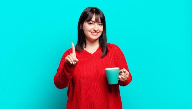 Plus la taille jolie femme souriante fièrement et en toute confiance faisant le numéro un pose triomphalement, se sentant comme un leader